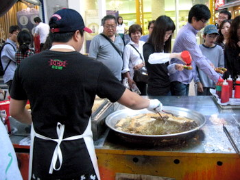 Street food vendor frying up fish cakes